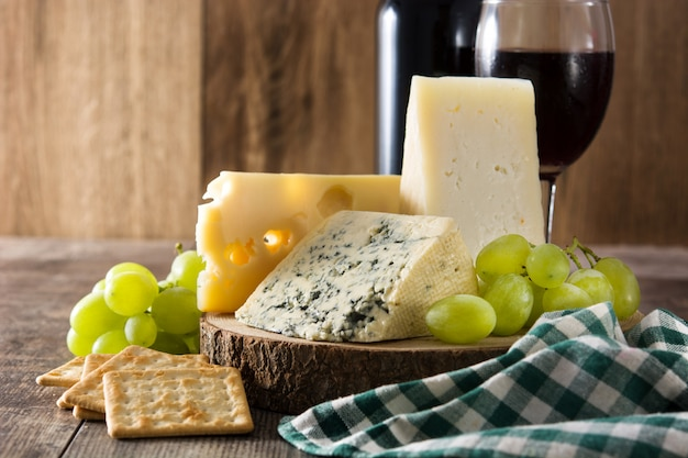 Assortment of cheeses and wine on wooden table.