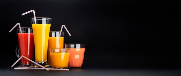Assortment of citrus cocktails on black with copy space