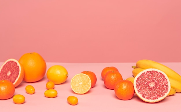 Assortment of citruses on pink table