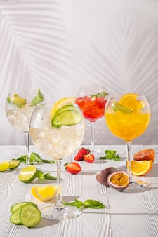 Assortment of cold lemonades in wine glasses on wooden table in morning sunlight