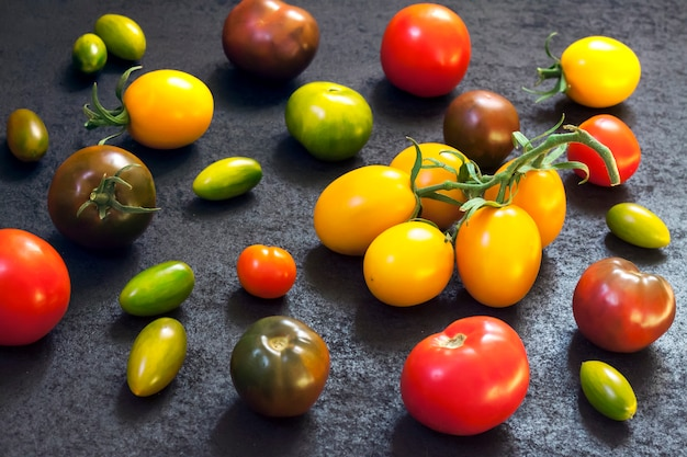 Assortment of colorful fresh tomatoes on black surface