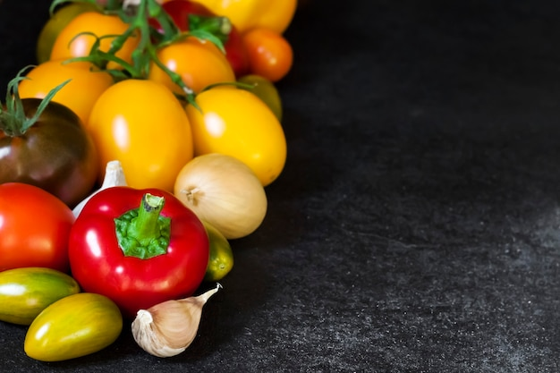 Assortment of colorful fresh vegetables on black background. copy space