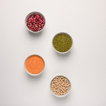 Assortment of colorful legumes in bowls lentils beans chickpeas mash on concrete surface top view