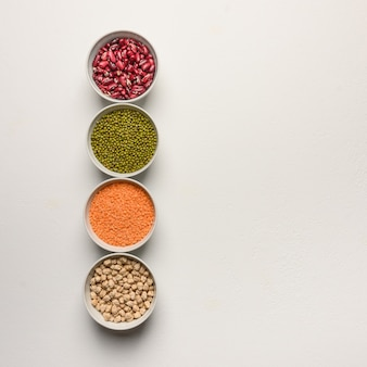 Assortment of colorful legumes in bowls lentils beans chickpeas mash on white surface top view