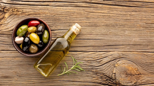 Assortment of colorful olives with oil bottle and copy space