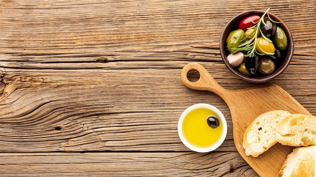 Assortment of colorful olives with oil saucer and copy space