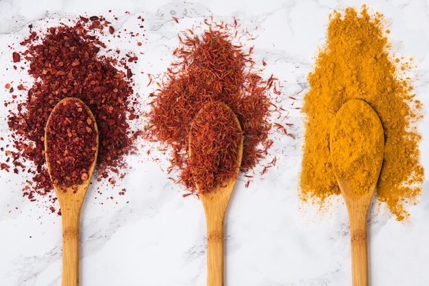 Assortment of colorful spices in the wooden spoons
