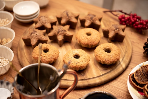 Assortment of cookies on wooden board with winterberry