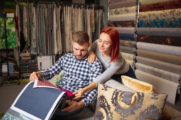 Ассортимент. пара, выбирая текстиль в магазине украшений для дома, магазине. оформление домашнего интерьера во время карантина. счастливые мужчина и женщина, молодая семья выглядят мечтательно, весело выбирая материалы.