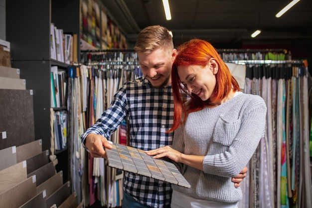 Assortment. couple choosing textile at home decoration store, shop. making of home interior design during quarantine. happy man and woman, young family look dreamful, cheerful choosing materials.