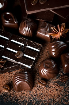 Assortment of dark, white and milk chocolate on rustic wooden sacking background.
