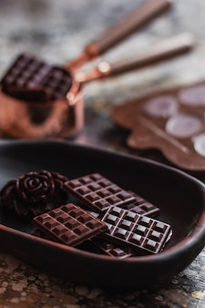 Assortment of different chocolate types inn wooden carved plate, with vintage props on the surface