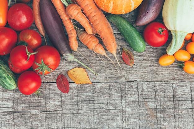 カントリースタイルの木製の背景にさまざまな新鮮な有機野菜の品揃え。健康食品ビーガン菜食主義のダイエットの概念。地元の庭はきれいな食べ物を生産します。フレーム上面図フラットレイコピースペース。