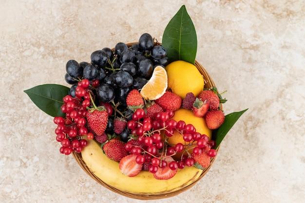 Un assortimento di diversi frutti e bacche in un cesto intrecciato su una superficie di marmo.