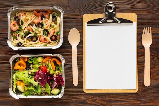 Assortment of different meals with empty clipboard