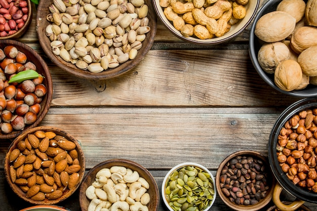Assortment of different nuts in bowls. on a wooden background.