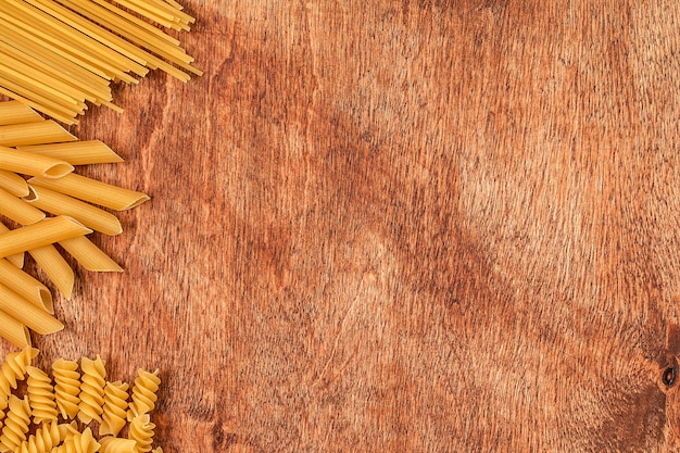 Assortment of different shape pastas on wood