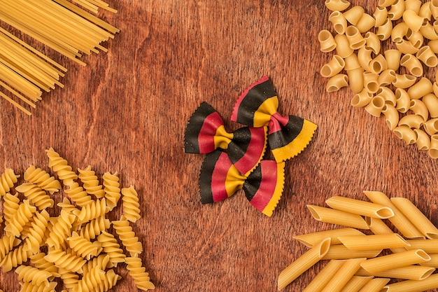 Assortment of different shape pastas on wooden table
