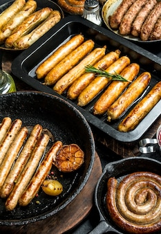 Assortment of different types of fried sausages. on black rustic.