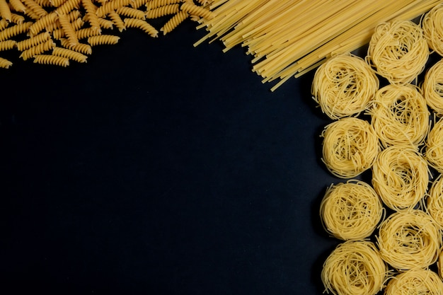 Assortment of different types of pasta dry on black background.