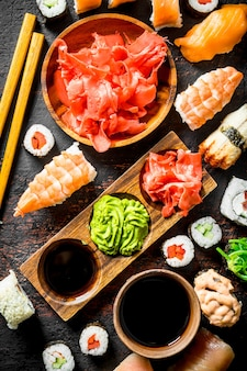 Assortment of different types of sushi, rolls and maki. on rustic surface
