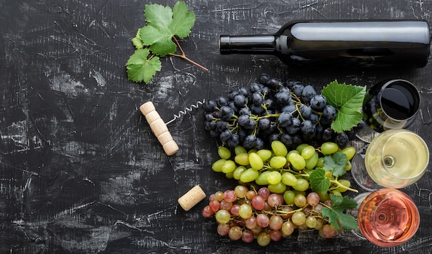 Assortment different types of wine and grade varieties. tasting white rose red wine in glasses near white pink and black grapes, red wine bottle on dark concrete background.