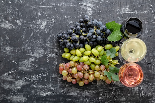 Assortment different types of wine and grape grade varieties. white rose red wine in wine glasses near white pink and black grapes. table wine on dark concrete background. tasting of alcoholic drinks.