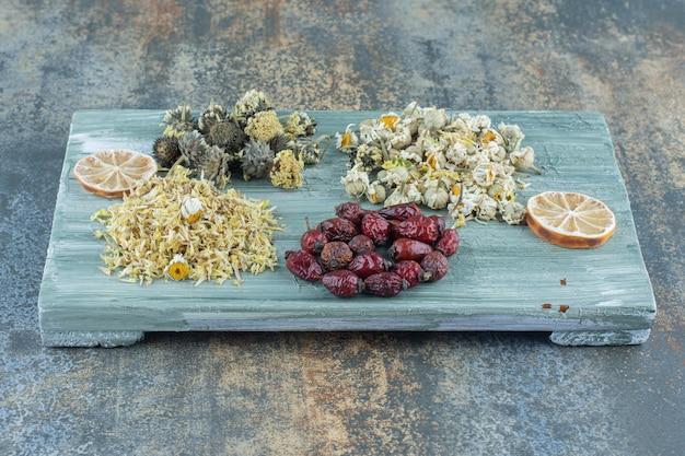 Assortimento di fiori secchi e cinorrodi su tavola di legno.