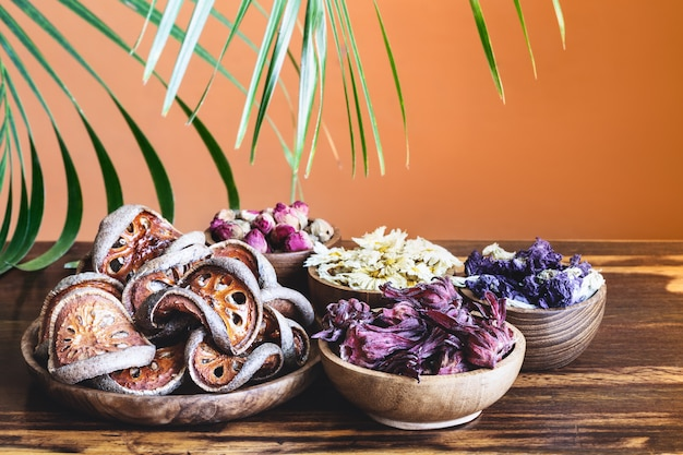 Assortment of dry herbal healthy tropical tea in wooden bowls and palm leaf on rustic background.