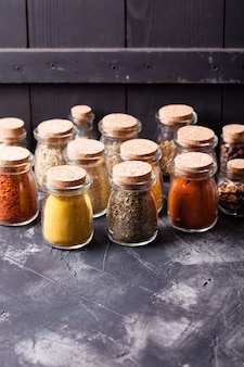 Assortment of dry spices in vintage glass bottles on white background