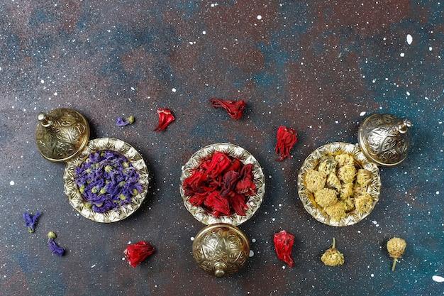 Assortment of dry tea in golden vintage mini plates. tea types background