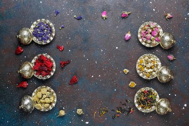 Assortment of dry tea in golden vintage mini plates.tea types