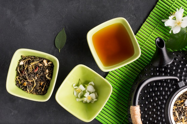 Assortment of dry tea herb on black slate backdrop