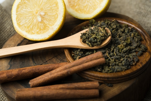 Assortment of dry tea herbs with halved lemons on wooden tray