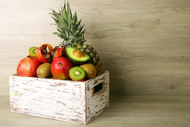 Assortment of exotic fruits in box on wooden background