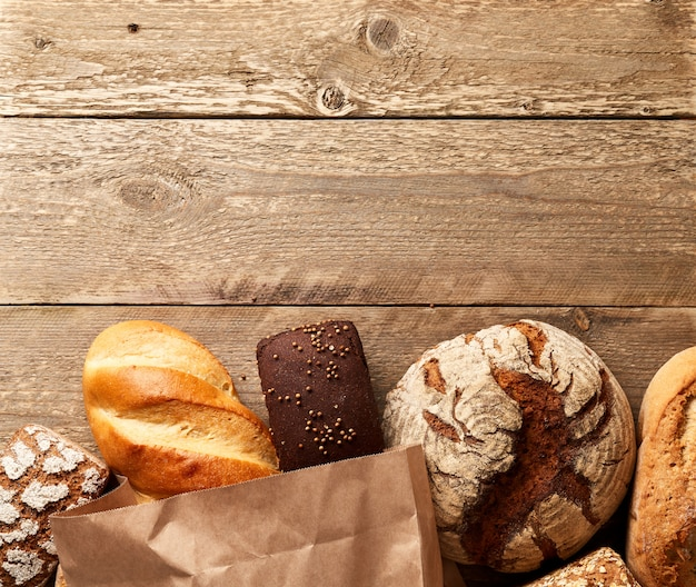 Assortment of fresh baked bread on a wooden background