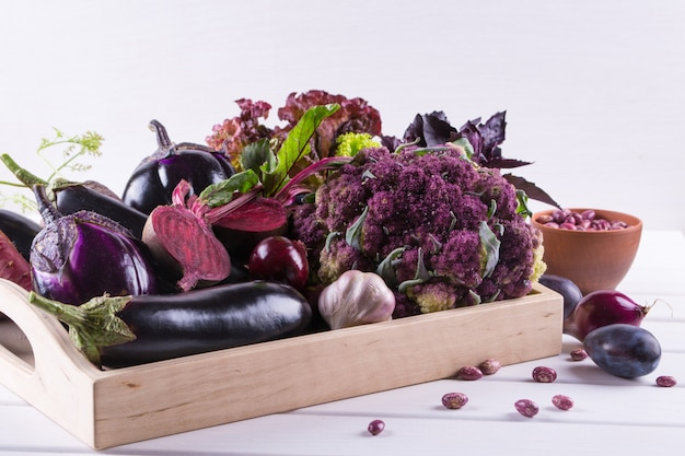 Assortment of fresh raw purple homegrown vegetables on dark wooden table. cauliflower, eggplant, beets, carrots, potatoes, plums, basil, onions, garlic, beans, lettuce.
