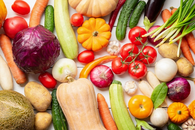 Assortment of fresh vegetables as a background. seasonal close up farmer table with vegetables. pumpkins, tomatoes, cabbage, carrots, onion, cucumber, melon, eggplant, potatoes and other.