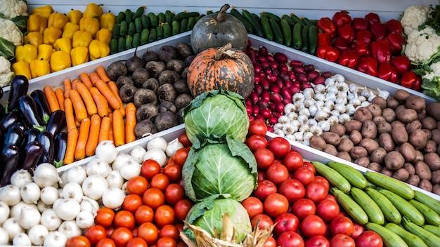 Assortment of fresh vegetables at market counter,
