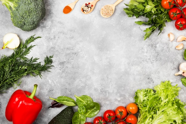 Assortment of fresh vegetables and spices on a light background