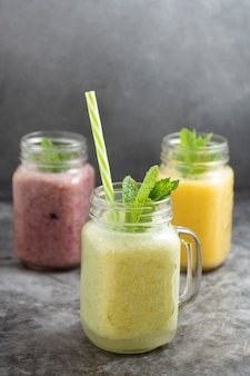 Assortment of fruit smothie in glass jars, summer refreshing drinks.