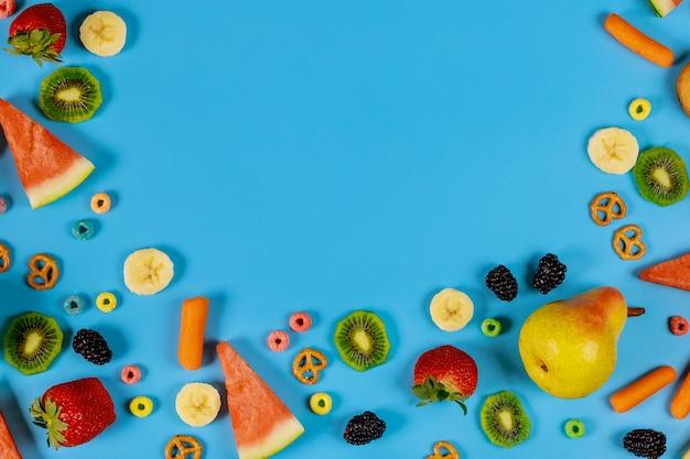 青色の背景に品揃えの果物と野菜。健康食品のコンセプトです。