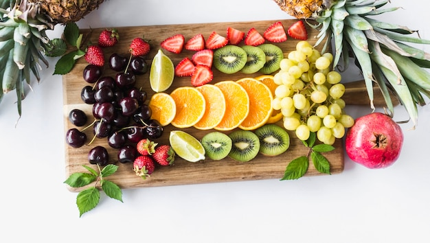 Assortment of fruits on chopping board over white background