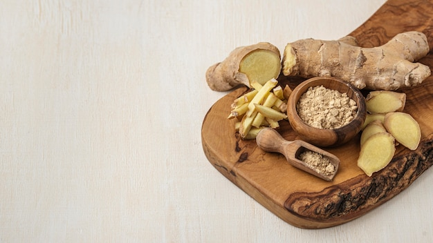 Assortment of ginger on wooden board with copy space