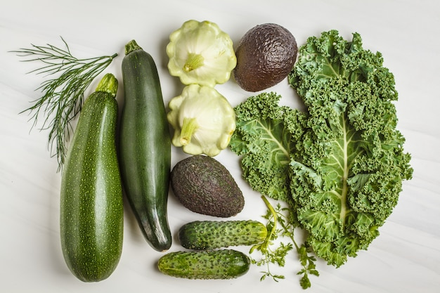 Assortment of green vegetables on white background, top view.