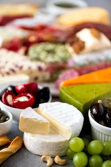 Assortment of hard, semi-soft and soft cheeses with olives, grissini bread sticks, capers, grape. cheese selection appetizer plate.