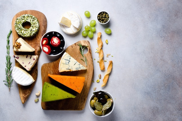 Assortment of hard, semi-soft and soft cheeses with olives, grissini bread sticks, capers, grape, on grey concrete backgound.