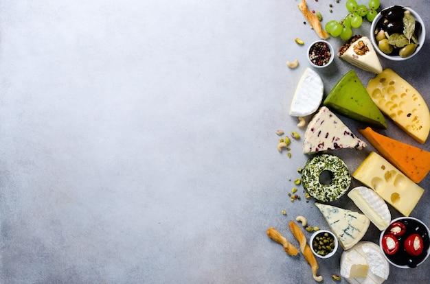 Assortment of hard, semi-soft and soft cheeses with olives, grissini bread sticks, capers, grape, on grey concrete.