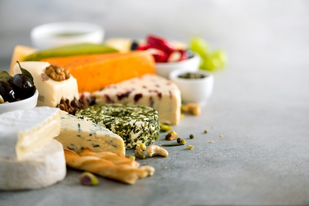 Assortment of hard, semi-soft and soft cheeses with olives, grissini bread sticks, capers, grape