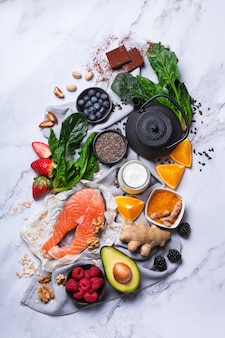 Assortment of healthy feel good food, superfood ingredients for stress, anxiety, chronic fatigue, depression relieving, reducing, for relaxation on a kitchen table. top view flat lay background